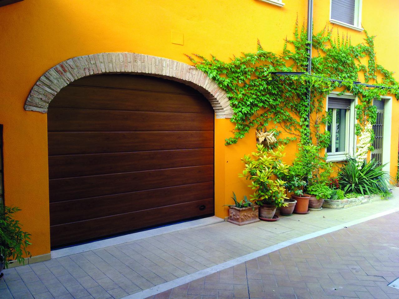 Sezionale quercia scura su parete aranzione con archetto di mattoni
